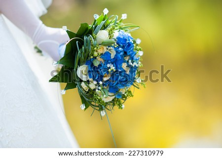 Closeup of bride's hand holding a wedding bouquet in spring outdoors - stock photo