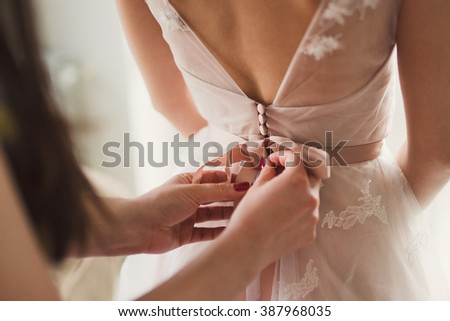 Closeup of bridesmaid tying bow on bride's dress - stock photo