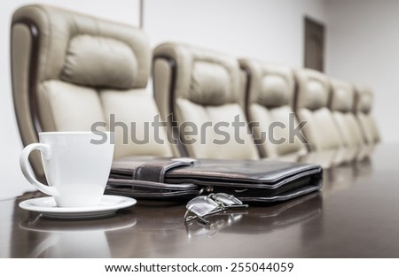 Closeup of briefcase, cup and glasses on table in empty corporate conference room before business meeting in office - stock photo