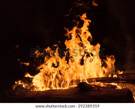 Closeup of bright golden color flames from a campfire at night - stock photo