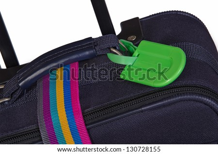 Closeup of bright green luggage tag and colorful belt on dark blue suitcase - stock photo