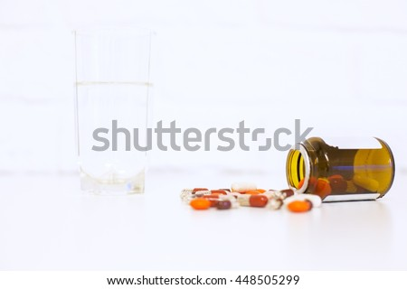 Closeup of bright tabletop with glass of water and medicine falling out of prescription bottle on white brick background - stock photo