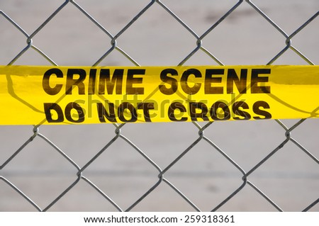Closeup of Bright yellow Crime Scene Do Not Cross tape against a chain link fence - stock photo