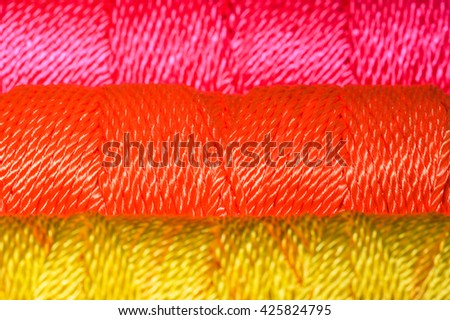 Closeup of Brightly colored nylon cord on a spool - Yellow, Orange, Pink - stock photo