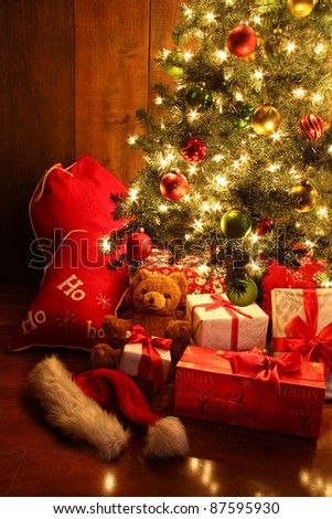 Closeup of brightly lit Christmas tree with gifts - stock photo