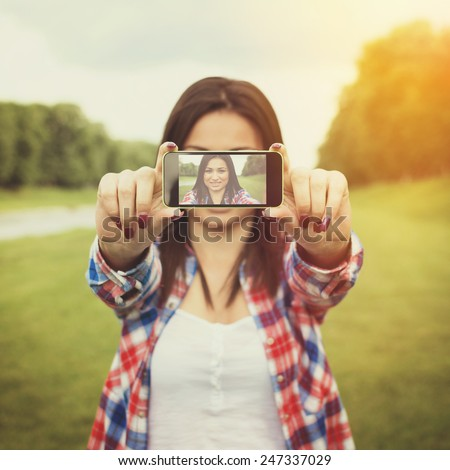 Closeup of brunette mixed race teenage girl taking a selfie with smartphone outdoors on sunny summer day. Square format, filter applied, warm colors. - stock photo