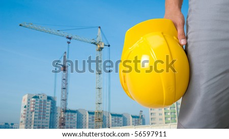Closeup of builder with yellow helmet on building panorama background - stock photo