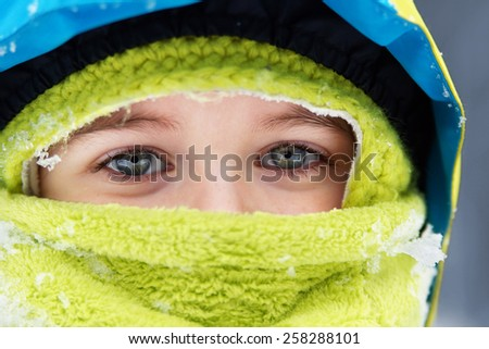 Closeup of bundled up blue eyed little boy with snow flakes details             - stock photo