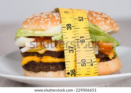 Closeup of burger wrapped in measuring tape - stock photo