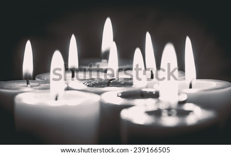 Closeup of burning candle on the black background, black and white - stock photo