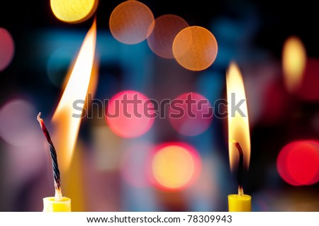 Closeup of burning candles front of multi-colored lights - stock photo