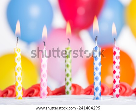 Closeup of burning colorful birthday candles on top of a cake with balloons in background