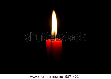 Closeup of burning red candle isolated on black background - stock photo