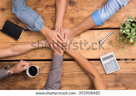 Closeup of business colleagues with their hands stacked. Business team showing unity with their hands together. Close up of business partners making pile of hands at meeting. Business team work. - stock photo