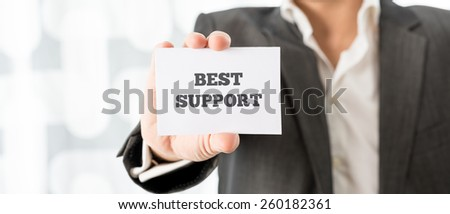 Closeup of business consultant showing a white card with Best support sign. - stock photo