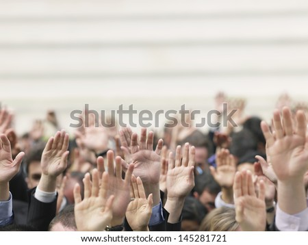 Closeup of business crowd raising hands - stock photo