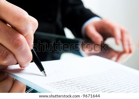 Closeup of business lady's hand with pen signing a contract on the background of her other hand touching the table - stock photo