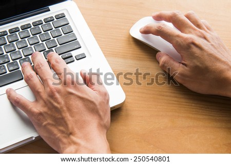 Closeup of business man hand typing on laptop keyboard