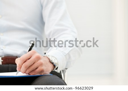 Closeup of business man writing form on clipboard at office - stock photo
