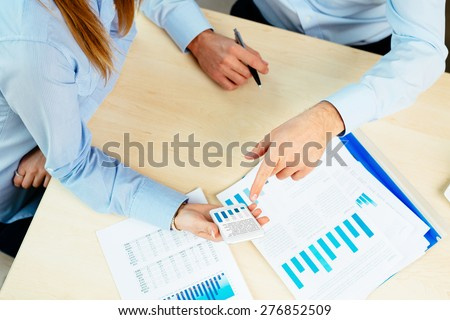 Closeup of business people checking financial data on smartphone and documents - stock photo