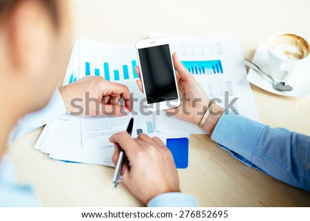 Closeup of business people discussing financial data over smartphone and documents with charts - stock photo