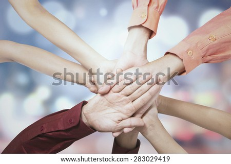 Closeup of business people joining hands together, shot against bokeh background - stock photo