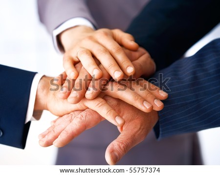 Closeup of business people's hands making a pile against a white background. - stock photo