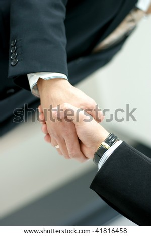 Closeup of business people shaking hands over - stock photo