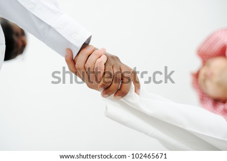 Closeup of business people shaking hands over a deal somewhere in the Middle east - stock photo