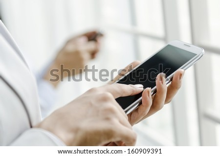 Closeup of business people using smart phone - stock photo