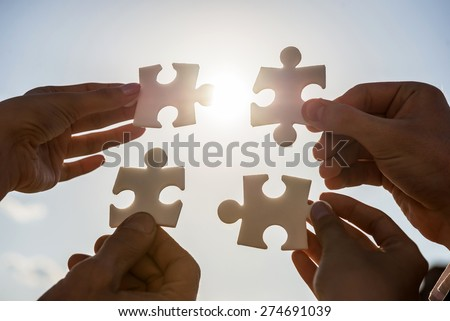 Closeup of business people wanting to put four pieces of puzzle together. - stock photo