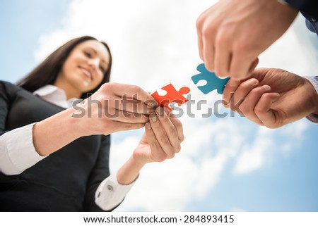 Closeup of business people wanting to put two pieces of puzzle together. Sky background.