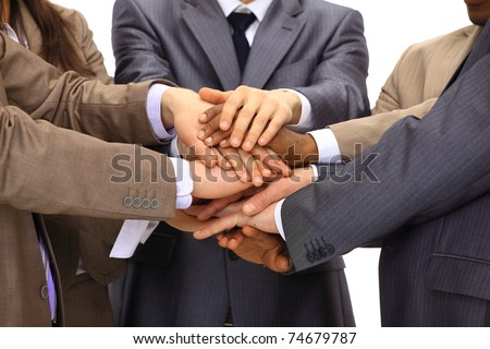 Closeup of business people with their hands together against a black background - stock photo