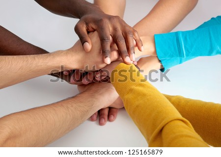 Closeup of business team putting their hands on top of each other - stock photo