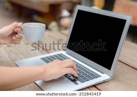 Closeup of business woman hand typing on laptop keyboard and coffee - stock photo