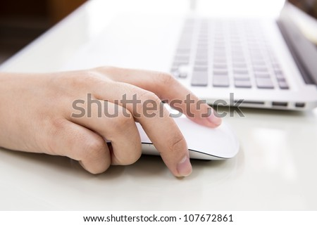 Closeup of business woman hand typing on laptop keyboard with mouse - stock photo