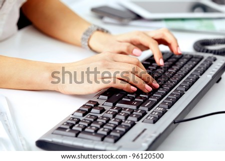 Closeup of business woman's hand typing on computer keyboard - stock photo