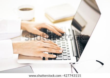 Closeup of business woman working on project on her laptop. Desktop with coffee and female hands writing report on laptop computer. Woman keyboarding on laptop during morning coffee break