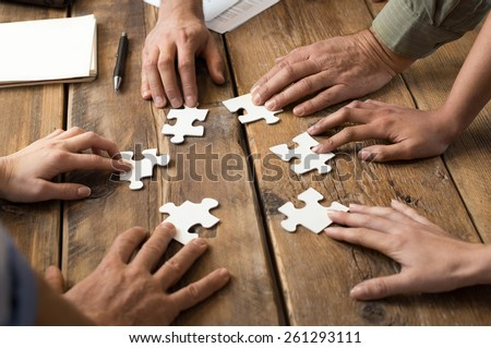 Closeup of businessman and woman with jigsaw puzzle pieces in office  - stock photo