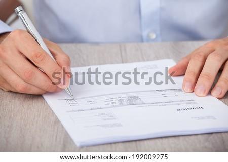 Closeup of businessman calculating accounts at desk - stock photo