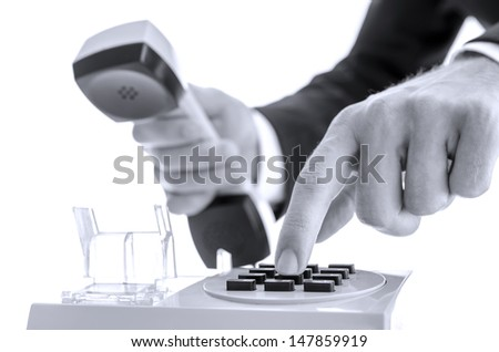 Closeup of businessman dialing a phone number on an old telephone. - stock photo