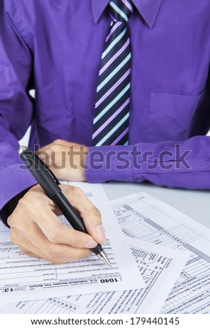 Closeup of businessman hand filling out a 1040 tax form - stock photo