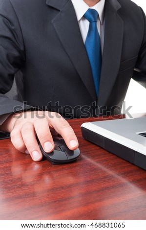 Closeup of businessman hand on mouse while working on laptop in his office