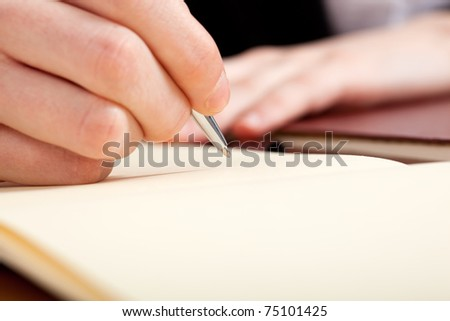 Closeup of businessman hand while writing a document