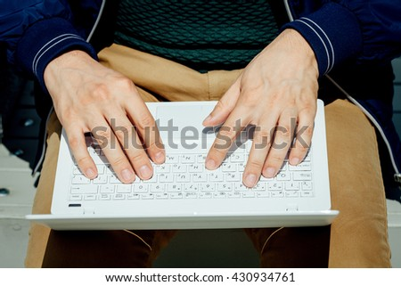 Closeup of businessman hands typing on laptop computer outdoors. Male typing on laptop in Park.