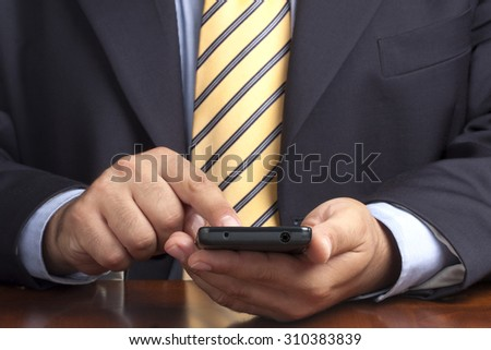 Closeup of businessman hands working on smartphone at desk