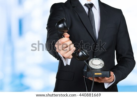 Closeup of businessman holding a telephone receiver - stock photo
