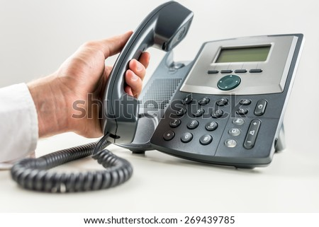 Closeup of businessman holding a telephone receiver about to make a phone call on landline telephone. Conceptual of customer service or telemarketing. - stock photo