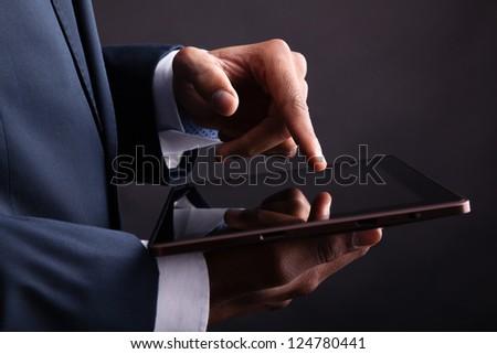 Closeup of businessman holding digital tablet on black background - stock photo