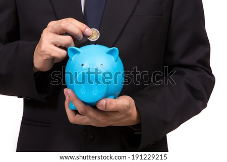 Closeup of businessman in a suit standing holding a blue piggy bank